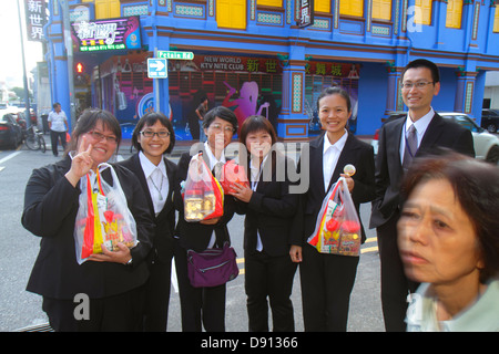 Singapore Little India Jalan Besar street scene shophouses Asian man woman shoppers photobomb - Stock Photo