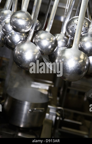 Ladles and saucepans in a restaurant kitchen. - Stock Photo
