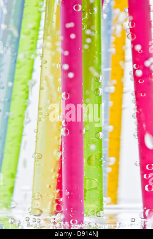 Colorful drinking straws in glass of water - Stock Photo