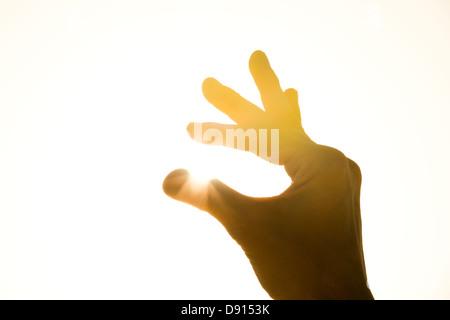 Human hand holding sun - Stock Photo