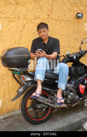 Singapore Singapore River Boat Quay Asian man using smart phone motorcycle sitting - Stock Photo