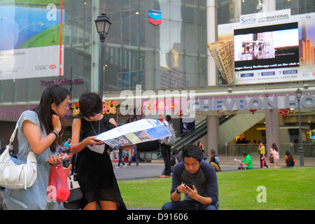 Singapore Raffles Place central business financial district plaza Asian woman map man smart phone - Stock Photo