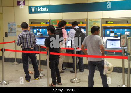 Singapore Farrer Park MRT Station subway train public transportation commuters riders Asian man ticket vending machine - Stock Photo