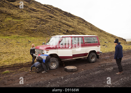 People changing flat tire of jeep - Stock Photo