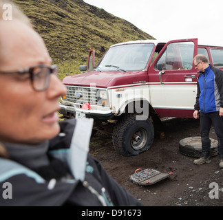 Changing flat tire of jeep - Stock Photo