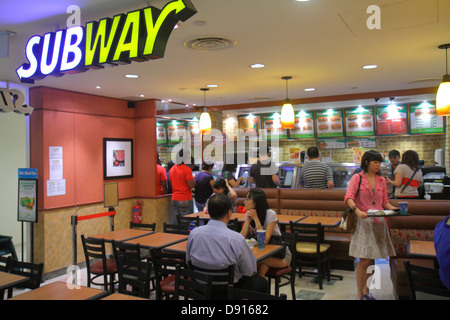 Singapore City Square Mall Subway sandwiches food restaurant tables inside interior Asian man woman - Stock Photo