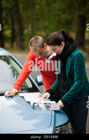 Young couple checking map on hood - Stock Photo