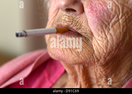 Old woman smoking, elderly woman smoker with a cigarette, elderly lady smoking - Stock Photo