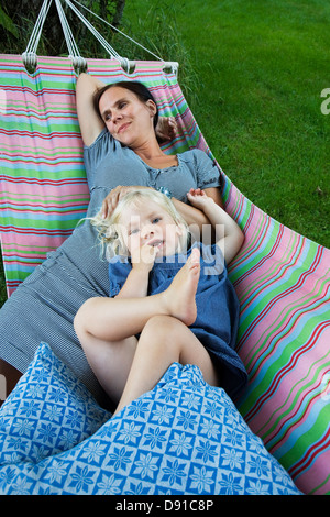 Mother and daughter resting in a hammock, Sweden. - Stock Photo