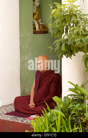 A Burmese Monk identifiable by his dark red robes sits in contemplation in a side alcove of the Shwedagon Pagoda - Stock Photo