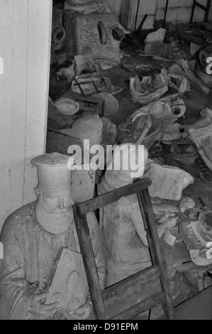 Statue of priest with bible among vandalized sculptures in the abandoned studio of artist Nikolaos Pavlopoulos. - Stock Photo