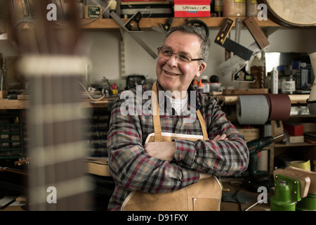 Guitar maker standing in workshop, smiling - Stock Photo