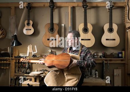 Guitar maker finishing acoustic guitar in workshop - Stock Photo