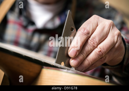 Close up of guitar maker finishing acoustic guitar in workshop - Stock Photo