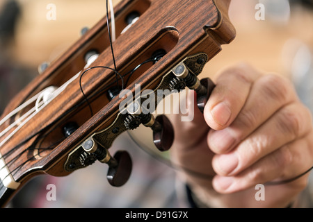 Close up of guitar maker tuning and testing acoustic guitar in workshop - Stock Photo
