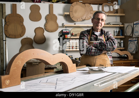 Guitar maker standing by acoustic guitar frame in workshop, portrait - Stock Photo