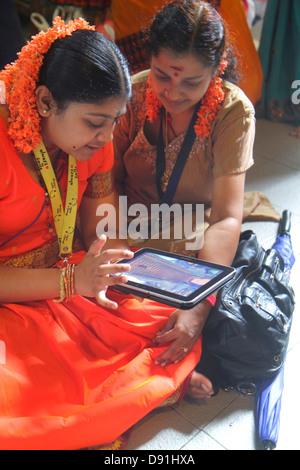 Singapore Little India Serangoon Road Sri Veeramakaliamman Temple Hindu Tamil Asian woman using iPad tablet - Stock Photo
