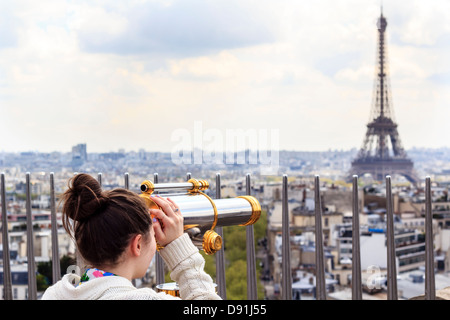 Girl looking at the Eiffel Tower through observation telescope on the rooftop of the Arc de Triump - Stock Photo