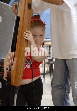 A young Cuban girl assisting her father to play an electric stand up bass - Stock Photo