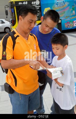 Bangkok Thailand Pathum Wan Rama 1 Road Asian man father boy son teen guide book pointing - Stock Photo