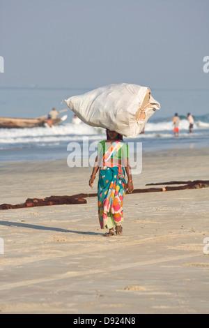 Asia, India, Goa, Benaulim, woman carries great heavy plastic sack on her head - Stock Photo