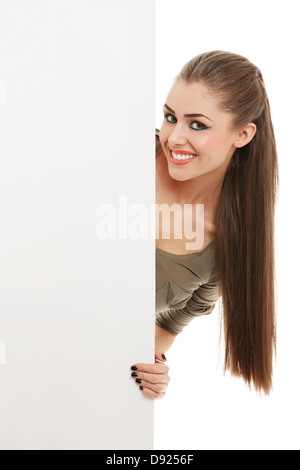 Portrait of smiling pretty woman peeking from behind vertical blank billboard sign over white background. - Stock Photo