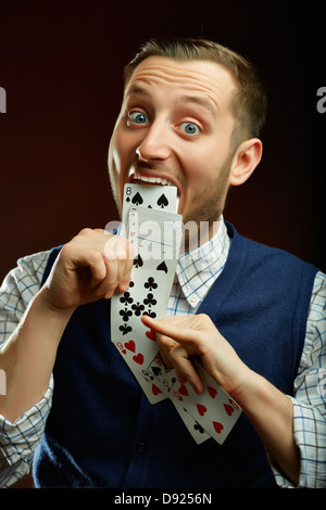Joyful funny male magician pulling out of his mouth a series of playing cards over dark background. - Stock Photo