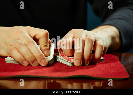 Male magician hands performing playing cards trick on casino table. - Stock Photo