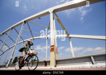 Man holding his hat while cycling, Amsterdam, the Netherlands - Stock Photo