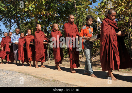 Buddhist Monks collecting alms at December full moon festival, Nyaungshwe, Inle Lake, Shan State, Myanmar - Stock Photo