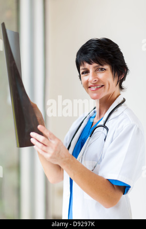 beautiful female middle aged doctor with x-ray in office - Stock Photo