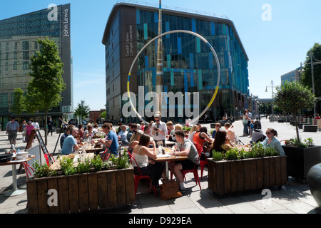 People sitting at tables outside in the street at Jamie's Italian Restaurant near John Lewis store and Cardiff Central - Stock Photo