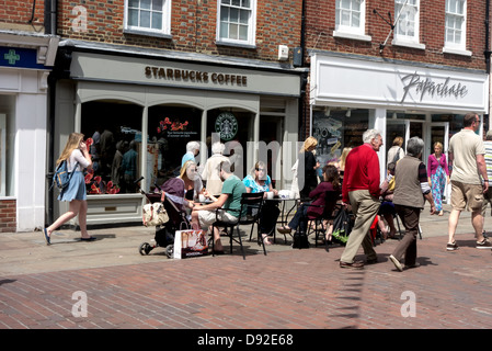 People enjoying a coffee sitting outside starbucks  coffee shop in chichester north sussex. - Stock Photo