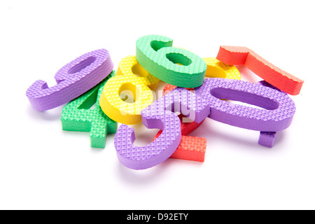 A pile of colorful numbers in children's foam on white background - Stock Photo