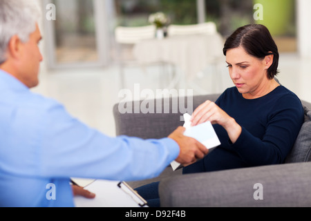 understanding therapist handing tissue to an upset middle aged patient - Stock Photo