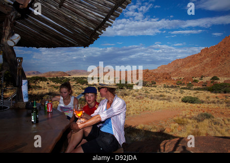 Family at bar at Fest Inn Fels Farm Lodge, Ranch Koiimasis, Tiras Mountains, Southern Namibia, Africa - Stock Photo
