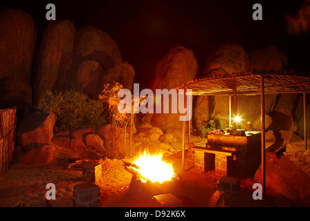 Campfire among the rocks, Ranch Koiimasis camp site, Tiras Mountains, Southern Namibia, Africa - Stock Photo