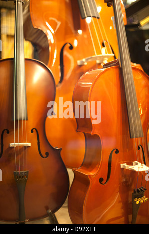 Cellos and an upright bass in a shop window display - Stock Photo