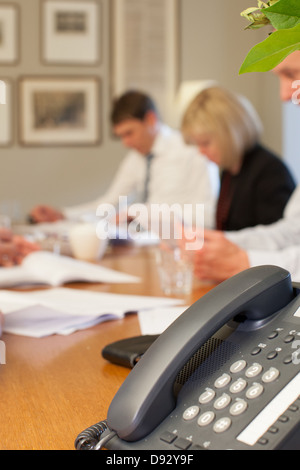 A business meeting in a corporate office setting, showing a telephone on the forefround, and people discussing in - Stock Photo