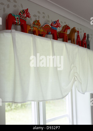 Traditional Scandinavian toy horses on shelf above window - Stock Photo