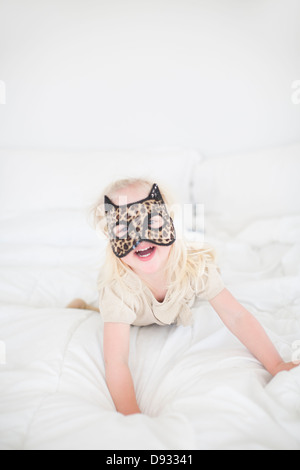 Girl wearing cat mask lying on bed - Stock Photo