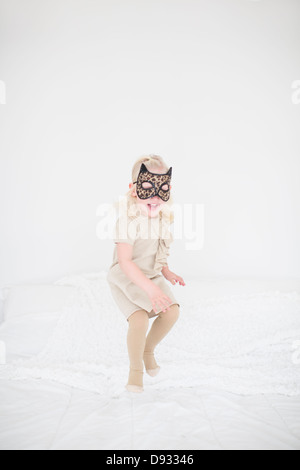 Girl wearing cat mask jumping on bed - Stock Photo