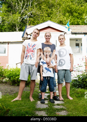 Mother and three sons standing in front of weekend cottage - Stock Photo