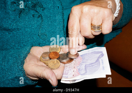 An old / elderly / senior woman's hands, holding and counting British money, by way of UK pound / pounds sterling - Stock Photo