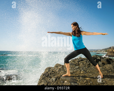 Mixed race woman practicing yoga on rocky beach - Stock Photo