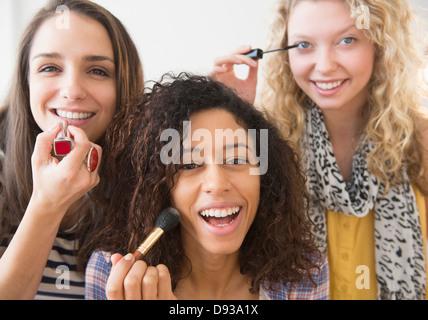Women applying makeup together - Stock Photo