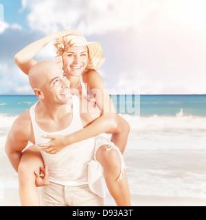 Happy couple on the beach, handsome man piggy back attractive woman, romantic date on seashore, luxury summer resort - Stock Photo