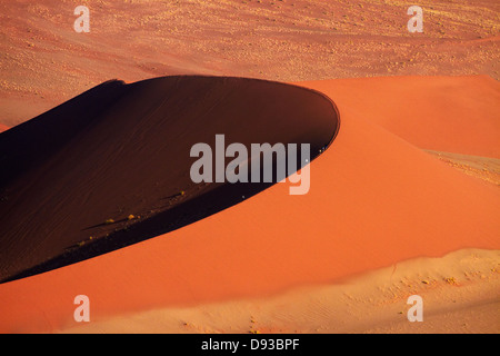 People climbing sand dune at Sossusvlei, Namib-Naukluft National Park, Namibia, Africa - Stock Photo