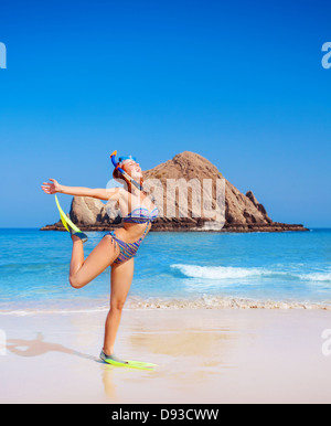 Cute happy woman wearing goggles and flippers, having fun on the beach, raised up hands, diving equipment, exotic - Stock Photo