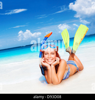 Happy diver woman lying down on beautiful sandy beach, wearing goggles, tube and flippers, having fun on summertime - Stock Photo